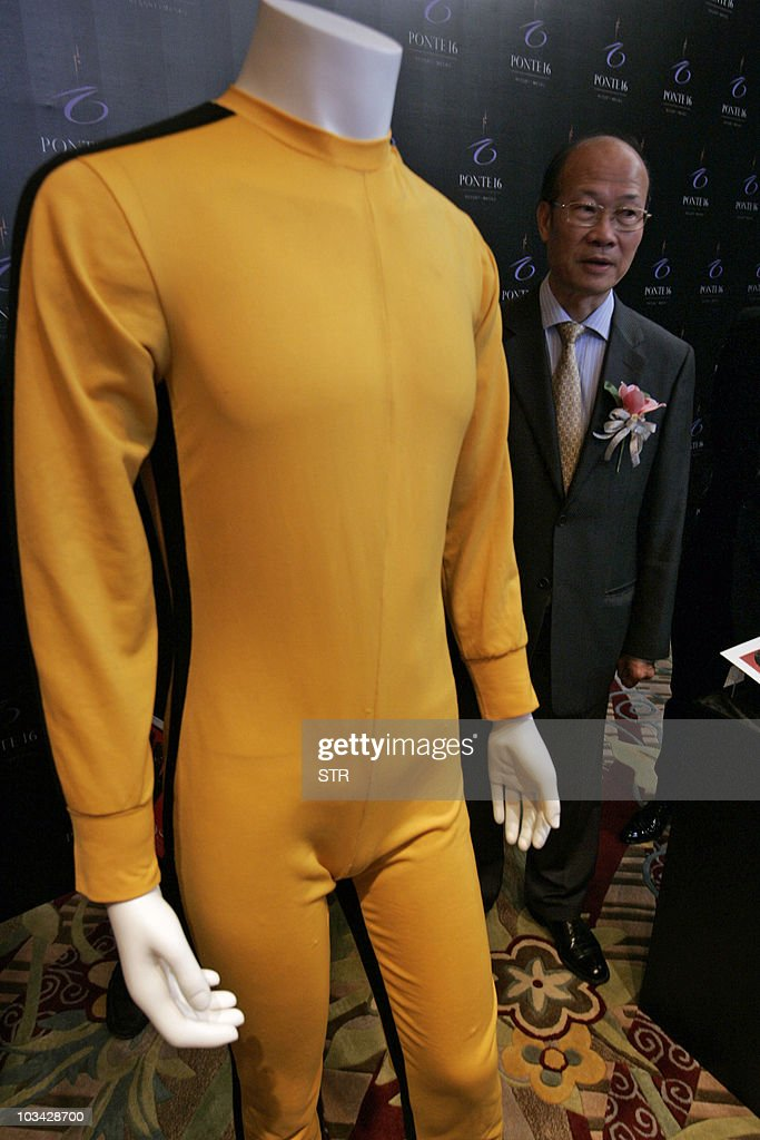 Ambrose So (R), chairman of 'Ponte 16', shows the late actor Bruce Lee's stunt double iconic yellow jumpsuit from the film 'Game Of Death', filmed in 1972 and released in 1978, at a media preview of pop memorabilia in Macau on August 18, 2010. The items are among several hundred pieces of memorabilia -- including an unused ticket to the iconic Woodstock music festival, Marilyn Monroe's bra, Elvis Presley's hair and a gown that belonged to Princess Diana -- that will go under the hammer at the October 9, 2010 auction in the glitzy Asian gambling hub.