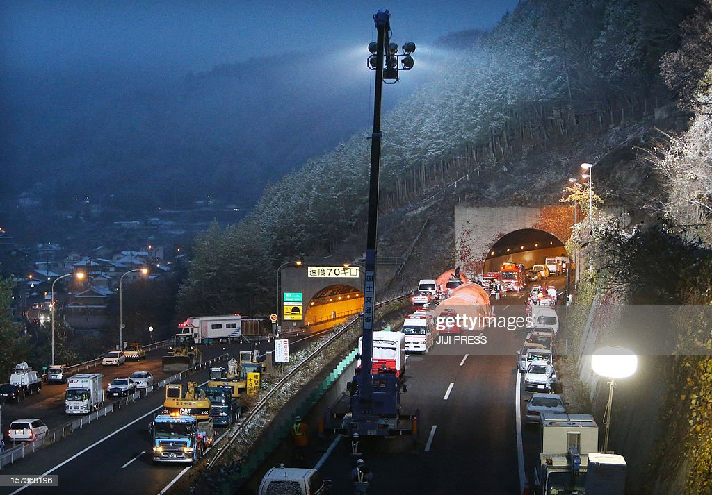 Ambulance and construction vehicles sit parked outside the Sasago tunnel in the city of Otsuki in Yamanashi prefecture, some 80 kms west of Tokyo on December 3, 2012, the morning after part of the tunnel collapsed, crushing cars and triggering a blaze inside. Rescuers found three crushed bodies in a collapsed tunnel on a major Japanese highway, taking the death toll to nine on December 3 as questions mounted about whether decaying ceiling supports caused the disaster. JAPAN