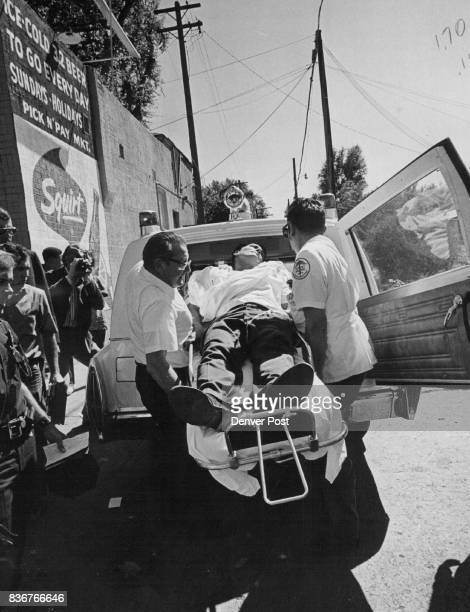 Ambulance attendants Robert Kreuzer left and Peter Chavez lift Roy Sedgebeer into ambulance about 2 pm Monday after he was shot in a holdup outside...