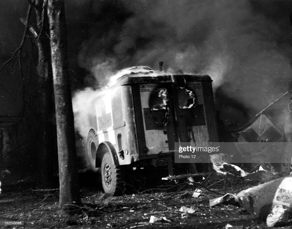 US Ambulance burning in motor pool of divisional medical clearing station hit by bomb from German plane at Nijmegen October 29 1944