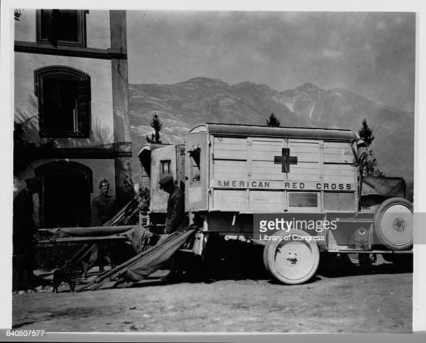 Ambulance drivers load stretchers onto American Red Cross ambulances at the 1st Line Hospital at the foot of Monte Grappa on the Italian front Ca...