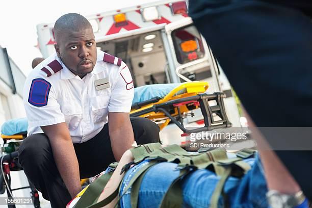 Ambulancia medics moving víctima en camilla