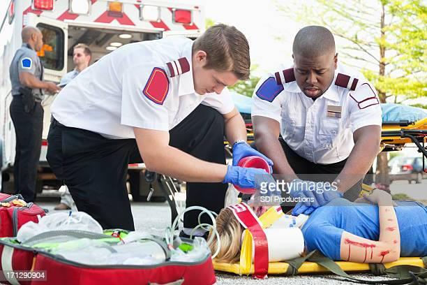 Ambulancia medics tratar mujer en camilla utilizando RCP