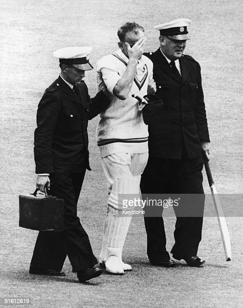 Ambulance officers helping England cricketer Frank Tyson leave the field after being struck in the head by a ball from Australian fast bowler Ray...