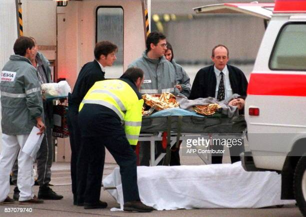 Ambulance personnel help load a wounded Swiss tourist arriving from Egypt on a chartered AirFrance into an ambulance in Zurich 19 November Ten...