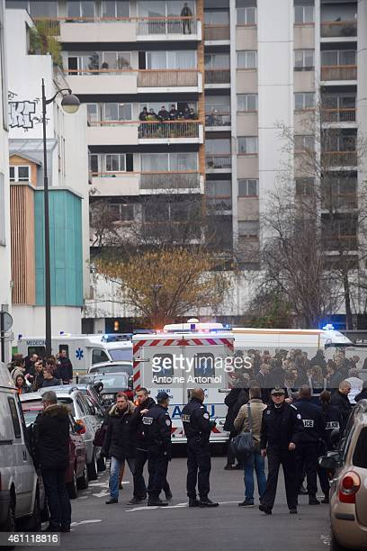 Ambulances and police officers gather in front of the offices of the French satirical newspaper Charlie Hebdo on January 7 2015 in Paris France Armed...