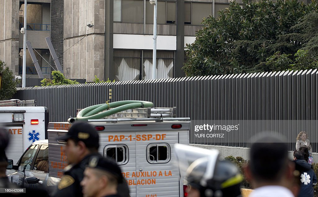 Ambulances are seen at the scene of the skyscraper that houses the headquarters of state-owned Mexican oil giant Pemex in Mexico City on January 31, 2013, following a blast inside the building. An explosion rocked the skyscraper, leaving up to now 14 dead and 40 injured, as a plume of black smoke billowed from the 54-floor tower, according to official sources. AFP PHOTO/Yuri CORTEZ