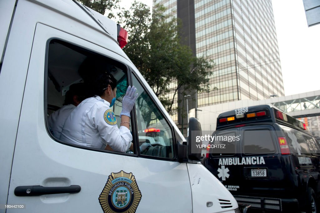 Ambulances arrive at the scene of the skyscraper that houses the headquarters of state-owned Mexican oil giant Pemex in Mexico City on January 31, 2013, following a blast inside the building. An explosion rocked the skyscraper, leaving up to now 14 dead and 40 injured, as a plume of black smoke billowed from the 54-floor tower, according to official sources. AFP PHOTO/Yuri CORTEZ