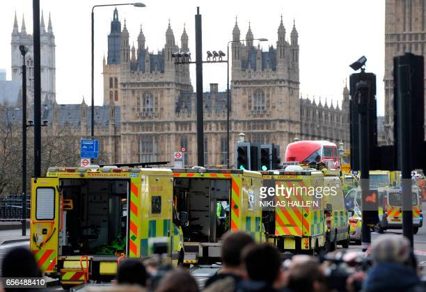 Ambulances wait as members of the emergency services work on Westminster Bridge alongside the Houses of Parliament in central London on March 22...
