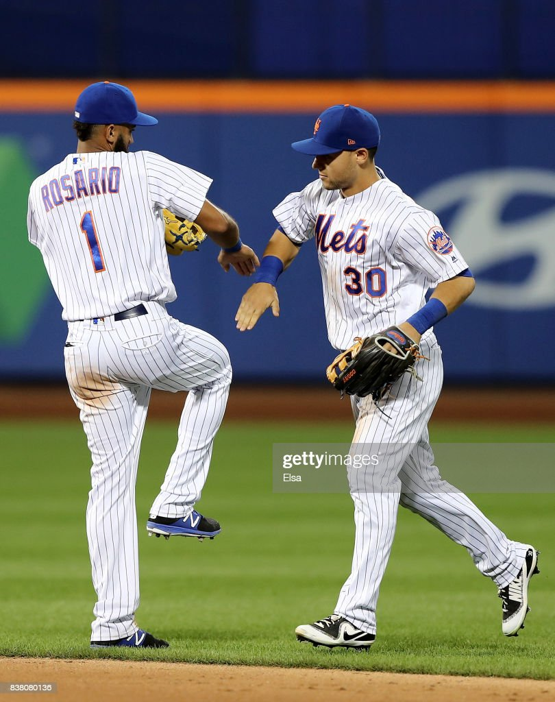 Amed Rosario #1 and Michael Conforto #30 of the New York Mets celebrate the 4-2 win over the against the Arizona Diamondbacks on August 23, 2017 at Citi Field in the Flushing neighborhood of the Queens borough of New York City.