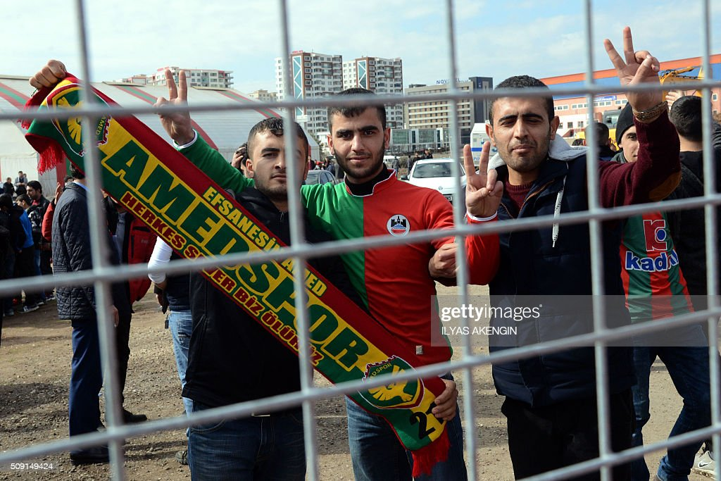 Amedspor's supporters gesture and wave scarves to cheer their team prior to the Turkish Cup football match between Amed Spor and Fenerbahce Zirrat on February 9, 2016 in Diyarbakir. The Turkish Football Federation said on February 5, 2016 it had suspended a Kurdish player for statements considered 'ideological propaganda' on the conflict in the Kurdish-majority southeast, adding to a string of cases cracking down on freedom of expression in Turkey. AKENGIN