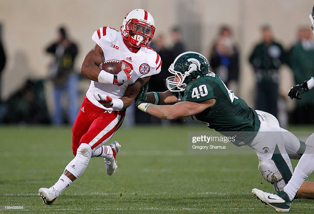 Ameer Abdullah #8 of the Nebraska Cornhuskers tries to get around the tackle of Max Bullough #40 of the Michigan State Spartans during a fourth quarter run at Spartan Stadium Stadium on November 3, 2012 in East Lansing, Michigan.