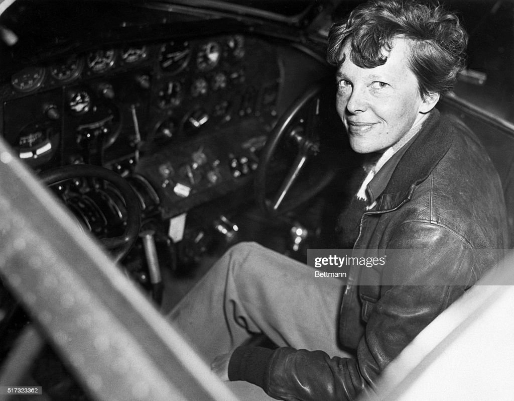 Amelia Earhart smiles as she sits clad in a leather aviator's jacket in the cockpit of a small airplane. One of the world's most famous aviators, Earhart was the first woman to fly solo across the Atlantic Ocean in 1932. While attempting to fly around the world in 1937 Earhart and her co-pilot and navigator Frederick Noonan crashed in the Pacific Ocean and neither their bodies nor their plane were ever found.