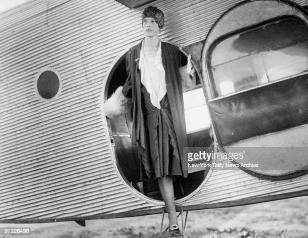 Amelia Earhart stepping out of the cabin of a plane at Curtiss Field