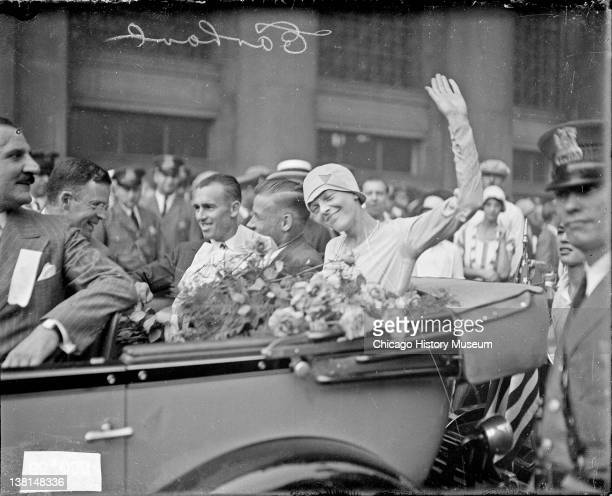 Amelia Earhart waving sitting with two men in the back seat of a convertible automobile Chicago Illinois 1928 From the Chicago Daily News collection