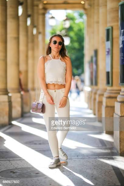 Amelie Lloyd fashion blogger wears a Jennyfer white lace top Jennyfer white pants an HM striped kimono jacket RayBan sunglasses a Valentino bag and...