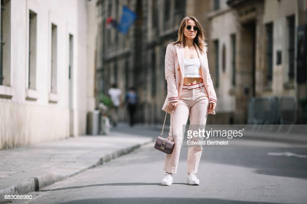 Amelie Lloyd fashion blogger wears a Journee pink suit a Primark white top a Valentino bag and white sneakers on May 13 2017 in Paris France