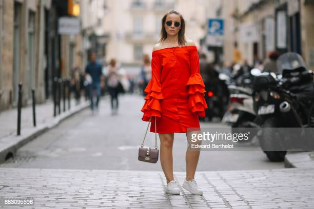 Amelie Lloyd fashion blogger wears a Journee red ruffled dress a Valentino bag sunglasses and white sneakers on May 13 2017 in Paris France