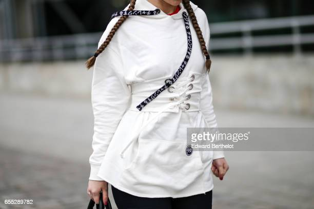 Amelie Lloyd fashion blogger wears Sandro black flared pants a Jennyfer white pull over with a hood and the printed inscription 'Let's try the Asian...