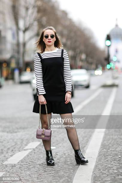 Amelie Lloyd fashion blogger wears sunglasses a Dahlia Girls black dress with a striped collar fishnet tights a Valentino rockstud bag and New Look...