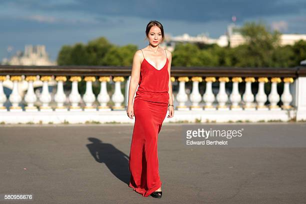 Amelie Lloyd is wearing a Maison Lemoine red dress and Balmain shoes during a street style session on the bridge Alexandre iii on July 25 2016 in...