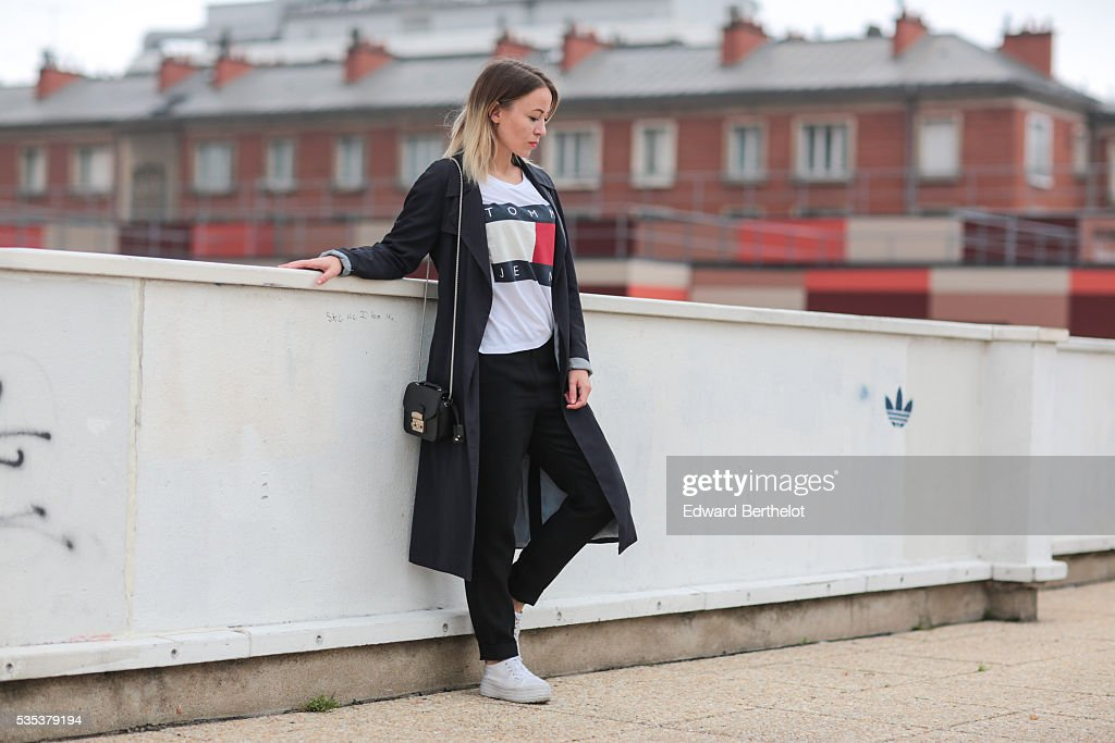 Amelie Lloyd (fashion blogger @ameetslloyd) is wearing a Zara trench coat, And Other Stories black pants, a Tommy Hilfiger t-shirt, and a Furla black bag, during a street style session on May 29, 2016 in Paris.