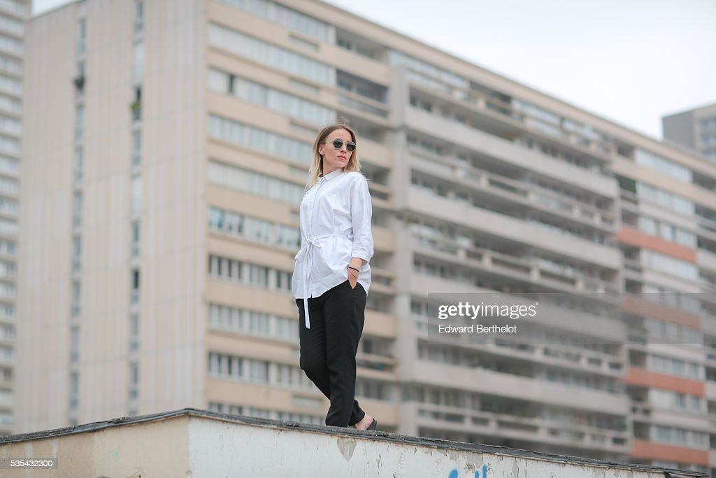 Amelie Lloyd (fashion blogger @ameetslloyd) is wearing And Other Stories black pants, a Cos white blouse, and a Furla black bag, during a street style session on May 29, 2016 in Paris.