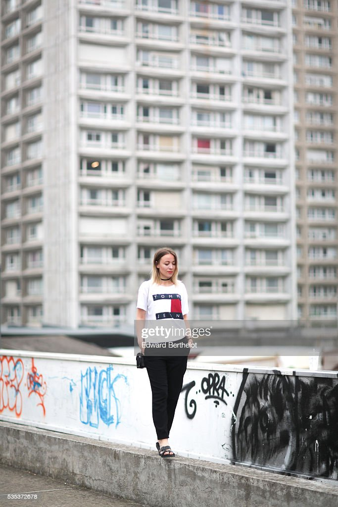 Amelie Lloyd (fashion blogger @ameetslloyd) is wearing And Other Stories black pants, a Tommy Hilfiger t-shirt, and a Furla black bag, during a street style session on May 29, 2016 in Paris.
