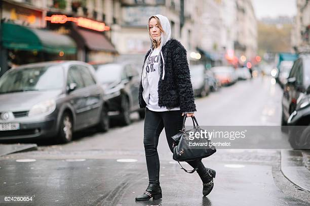 Amelie Lloyd is wearing Sandro black denim jeans a white tshirt with the inscription 'French Do It' a Jennyfer hoodie a Zara faux fur coat a...