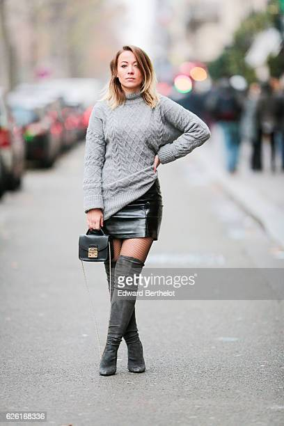 Amelie Lloyd is wearing Zara tigh high boots an HM gray oversized pull over a New Look black shiny skirt Topshop tights and a Zara gray long coat on...
