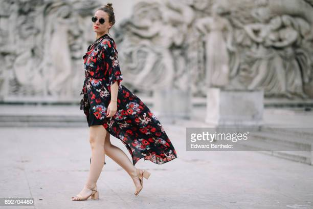 Amelie Lloyd wears a Kenzo flower print kimono dress Zara shoes sunglasses a Valentino Rockstud bag at Palais de Tokyo on May 30 2017 in Paris France