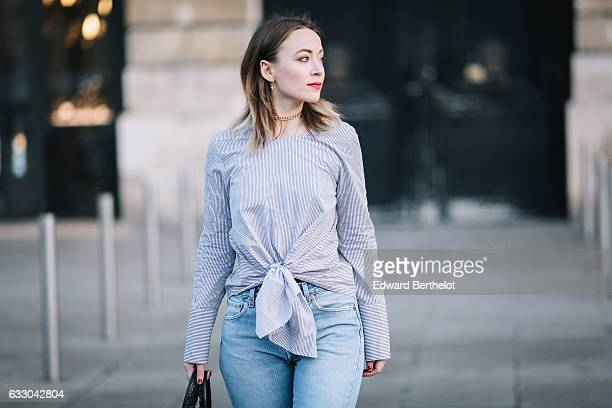 Amelie lloyd wears Newlook black shiny boots Levi's blue denim boyfriend jeans pants a Newlook blue and white striped shirt with a knot a Balenciaga...