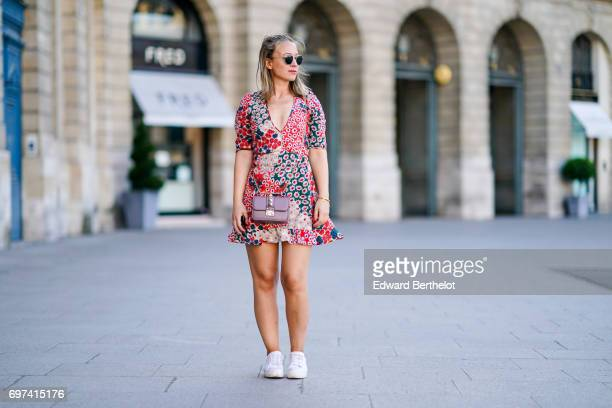 Amelie Lloyd wears Rayban sunglasses a flower print dress from Zara white sneakers and a Valentino bag at Place Vendome on June 17 2017 in Paris...