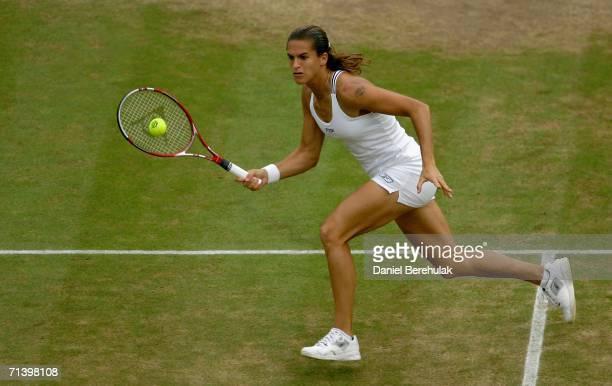 Amelie Mauresmo of France returns a forehand to Justine HeninHardenne of Belgium during the women's final match on day twelve of the Wimbledon Lawn...