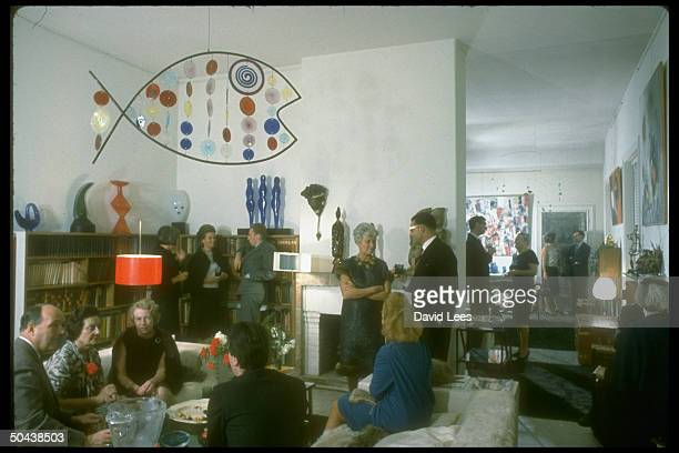 Amer expatriate and art patron Peggy Guggenheim hosting cocktail party in drawing room of her artfilled palazzo talking w unident guests