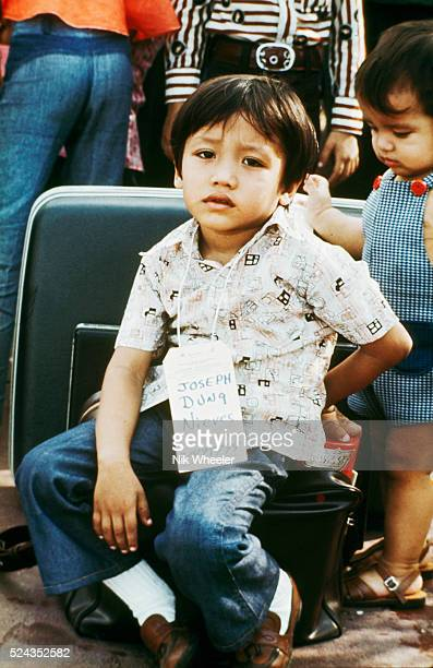 Amerasian boy with identity tag sits with his luggage outside the US Embassy in Saigon awaiting the orderly evacuation to Tan Son Nhut airport and a...