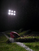 Amercian football on folded lawn on playing field