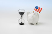 US, America time countdown economics, budget, saving or financial crisis concept, hourglass or sandglass with white piggy bank with United States national flag isolated on white background.