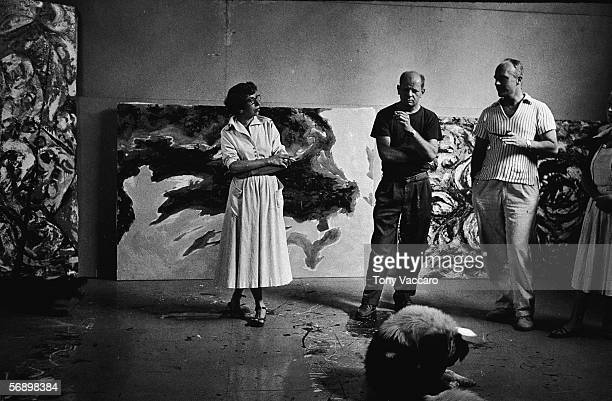 American abstract expressionist painter Jackson Pollock and his wife Lee Krasner and an unidentified couple stand around a dog and smoke in his...