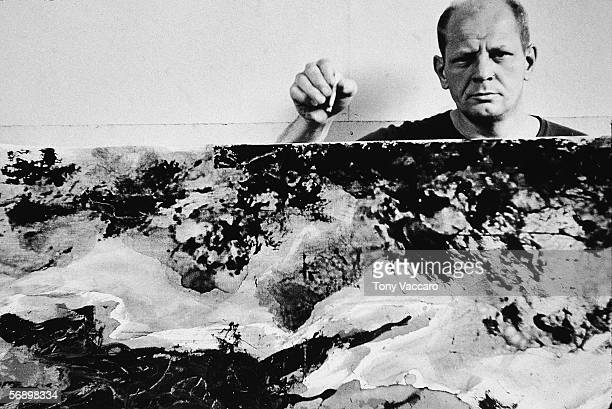 American abstract expressionist painter Jackson Pollock holds a cigarette above and behind one of his paintings in his studio at 'The Springs' East...