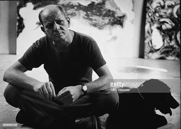 American abstract expressionist painter Jackson Pollock sits with a black dog possibly a curly coated retriever in his studio at 'The Springs' East...