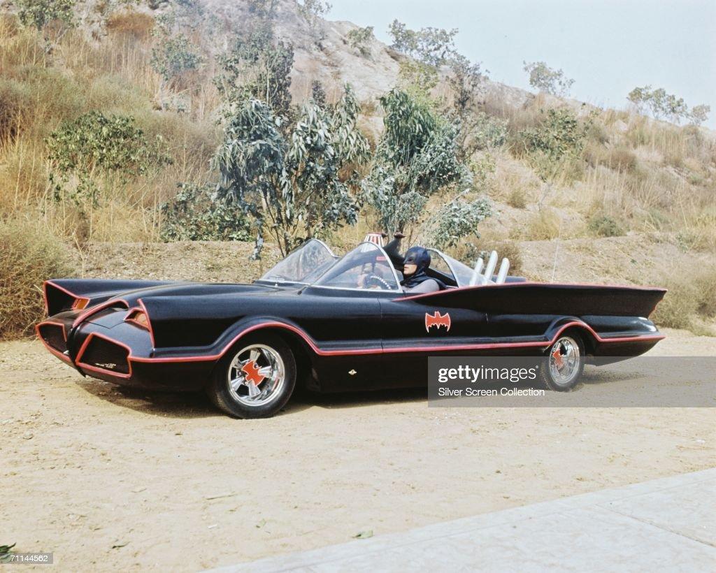 American actor Adam West as Bruce Wayne/Batman at the wheel of the Batmobile with passenger Burt Ward as Dick Grayson/Robin in the TV series 'Batman'...
