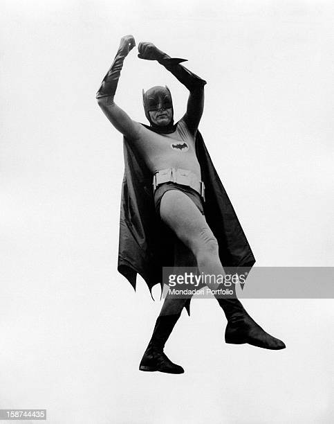 American actor Adam West wearing the costume of the comics superhero Batman letting himself down by flying in the TV serie Batman October 1966