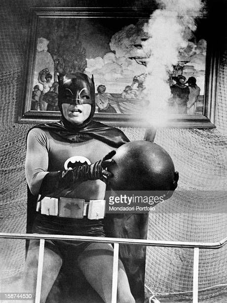 American actor Adam West wearing the costume of the comics superhero Batman and holding a bomb in the TV serie Batman 1966