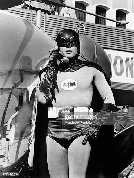 American actor Adam West wearing the costume of the comics superhero Batman and making a phone call in the TV serie Batman 1966