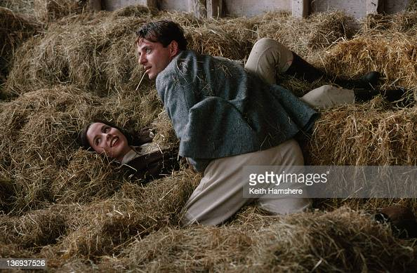 American actor Aidan Quinn and English actress Kate Beckinsale rolling in the hay in a scene from the film 'Haunted' 1995