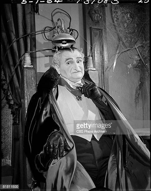 American actor Al Lewis in the role of 'Grandpa' wears evening dress and a cape as he sits in his electric chair in the CBS television situation...