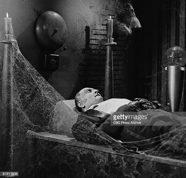 American actor Al Lewis in the role of 'Grandpa' wears evening dress as he sleeps in a cobwebbed room beneath a large alarm bell in a still from the...