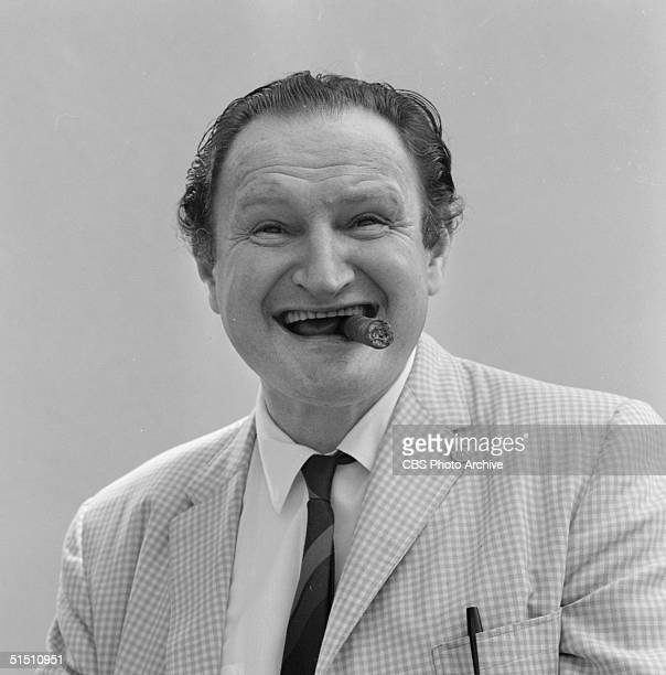 American actor Al Lewis smiles and smokes a cigar while he wears a checked jacket in this publicity photo for the CBS situation comedy 'The Munsters'...