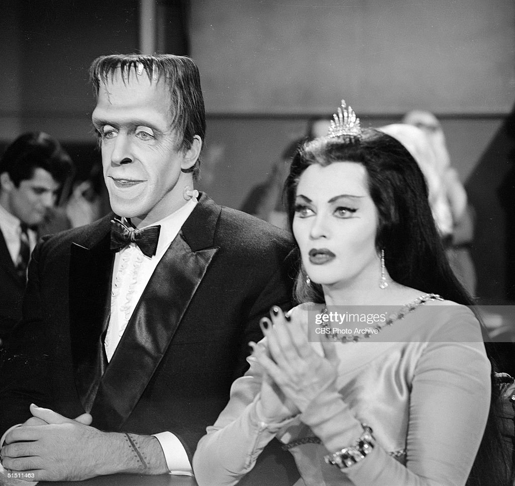 American actor and children's book author Fred Gwynne (1926 - 1993) (as Herman Munster) and Canadian actress Yvonne de Carlo (as Lily Munster) sit with rapt attention as they watch Lily's father's magic act in a still from the CBS television situation comedy 'The Munsters' episode 'Grandpa Leaves Home,' November 12, 1964. The epsiode first aired November 24, 1964.